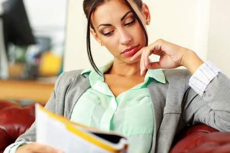 Businesswoman reading magazine in modern office Stock Photo