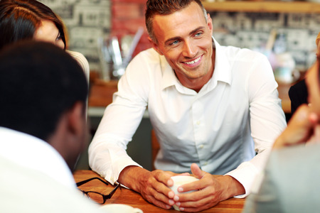 Happy business people having meeting around table in office Stock Photo