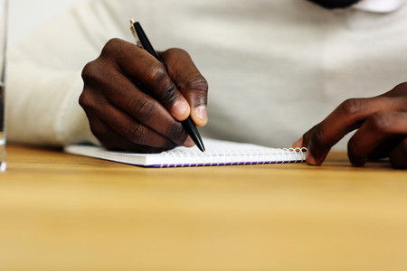 Closeup portrait of a male hand writing on a paper photo