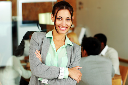 Happy businesswoman with arms folded standing in front of colleagues photo