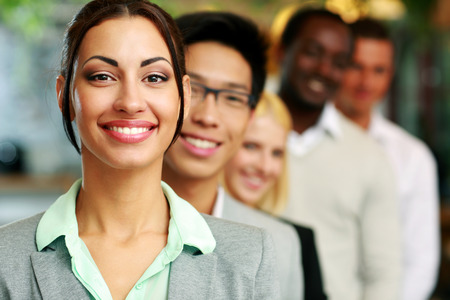 happy business team: Smiling businesswoman standing in front of colleagues