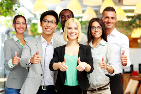 Smiling business group giving thumbs up photo