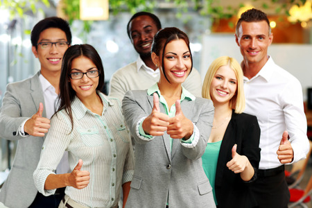 Happy business group giving thumbs up photo