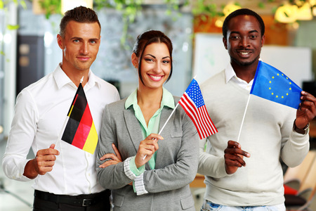 Happy group of businesspeople standing with flags in office photo