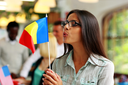 Businesswoman in glasses blowing on flag of Romania photo