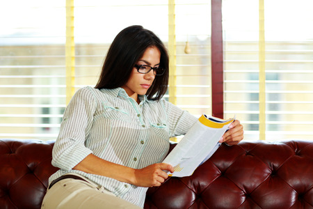 concetrated: Portrait of a young businesswoman in glasses reading something