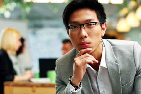 Portrait of a thoughtful asian man sitting in office, with his colleagues in background photo