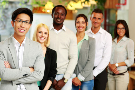 Portrait of a smiling asian businessman standing in front of colleagues photo