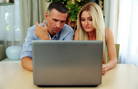 concetrated: Young couple using laptop together