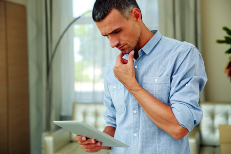 Handsome man standing and using tablet computer at home Stock Photo