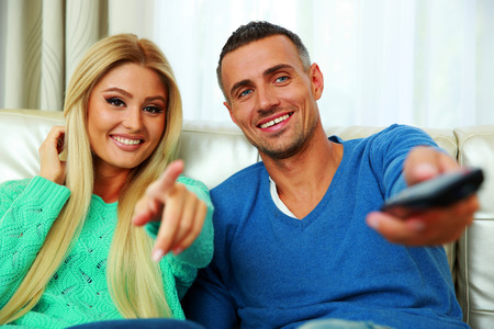concetrated: Happy young couple sitting on the sofa and watching TV