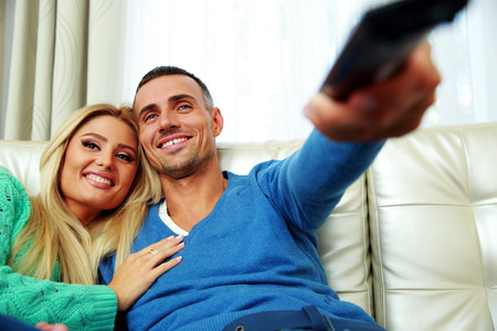 Cheerful young couple sitting on the sofa and watching TV Stock Photo