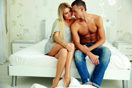 Young couple sitting on the bed a thome photo