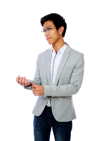 Portrait of a handsome asian man buttoning his jacket over white background photo