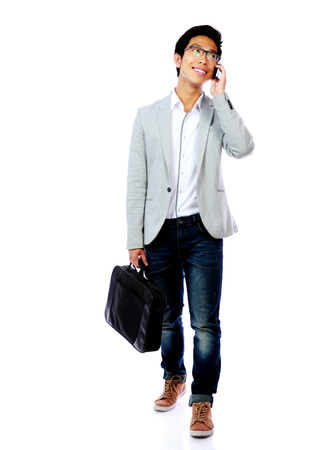 Full length portrait of asian man walking with laptop bag and speaking phone photo