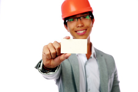 Young asian man with safety helmet holding blank card. Focus on card photo