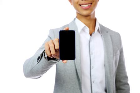 Smiling asian man holding smartphone over white background. Focus on smartphone photo