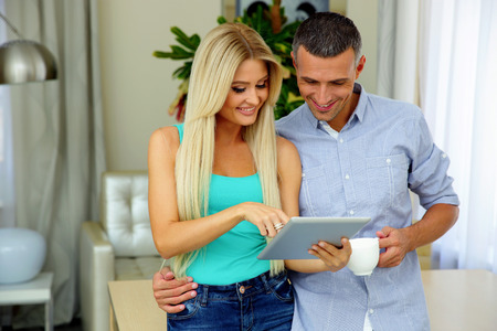 computer user: Happy couple with tablet computer and cup of coffee standing at home Stock Photo