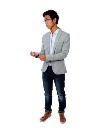 Full length portrait of a handsome asian man buttoning his jacket over white background photo