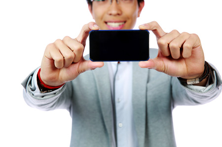 Happy asian man making photo on smartphone. Focus on smartphone photo