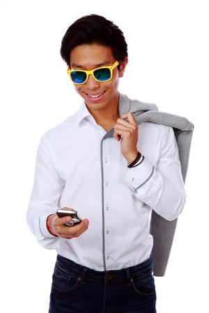 smarthone: Fashion asian man in sunglasses using smarthone over white background