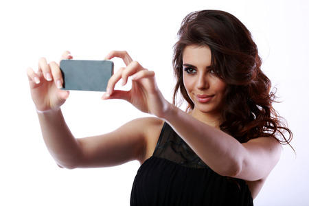 Beautiful woman taking self picture with smartphone camera photo