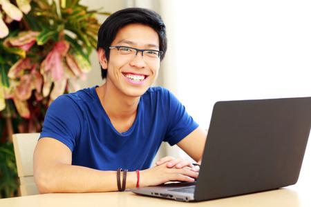 ノート パソコンとテーブルに座って陽気なアジア男