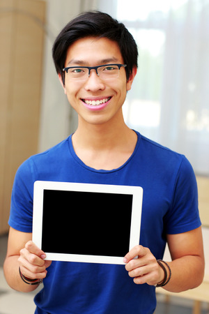 Young smiling asian man showing blank tablet computer screen at home photo