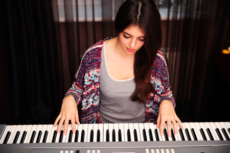 Young beautiful woman playing on piano at home 스톡 콘텐츠