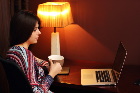 Beautiful woman holding cup of coffee and looking at laptop photo