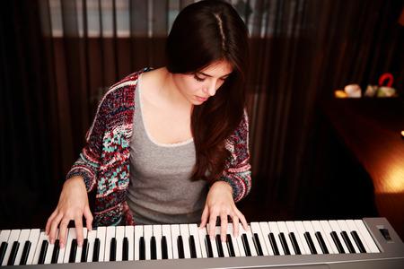 Junge schöne Frau spielen auf dem Klavier zu Hause
