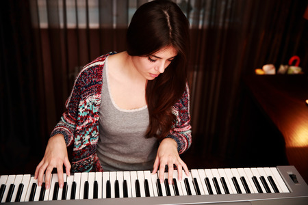 playing music: Young beautiful woman playing on piano at home Stock Photo