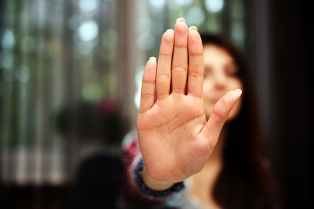 stop hand: Woman with her hand extended signaling to stop (only her hand is in focus)