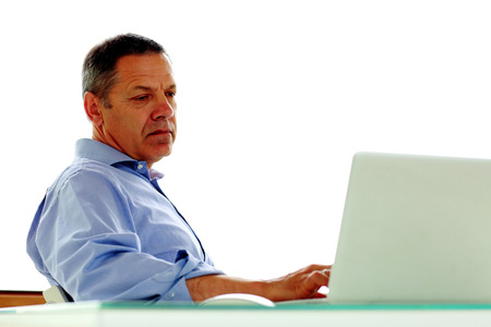Portrait of a middle aged caucasian man looking at his laptop computer. photo