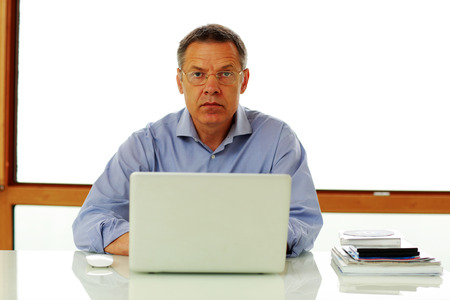 50 yrs: Portrait of a middle aged man sitting on the table with laptop computer. Stock Photo