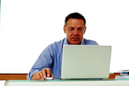 50 yrs: Portrait of senior caucasian man working on his laptop computer.