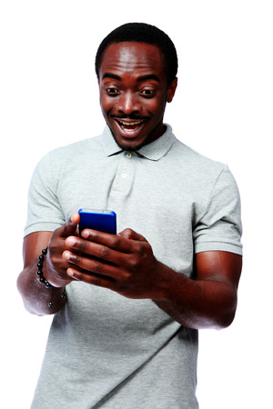 african man: Portrait of a laughing african man using smartphone over white background Stock Photo