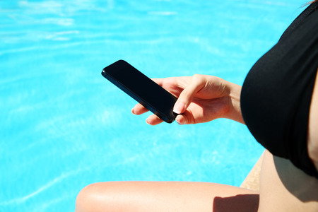 Closeup image of female hand using smartphone in swimming pool photo