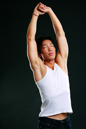 concetrated: Portrait of relaxed asian man stretching on black background