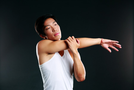 concetrated: Pensive asian man stretching hands on black background Stock Photo