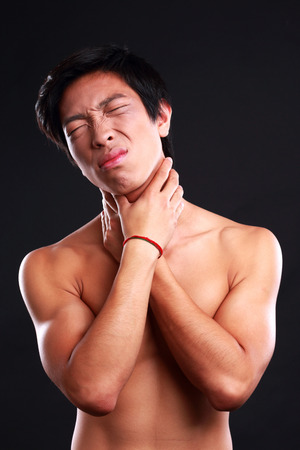Young male suffering from neck pain on black background photo