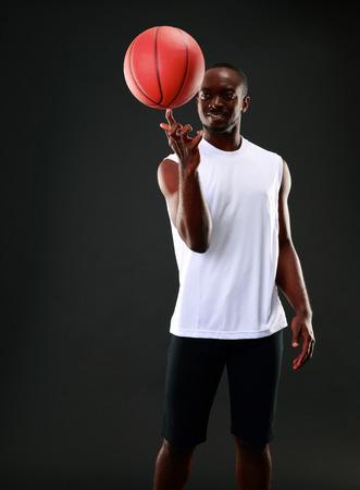 アフリカ青年バスケット ボールを彼の指につかまって 写真素材