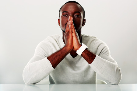 Portrait of a pensive african man sitting at the table photo
