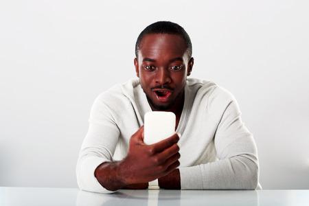 sorprendido: Hombre africano sorprendido que se sienta en la mesa y mira smartphone