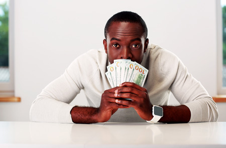 american banker: Portrait of african man sitting at the table and holding US dollars
