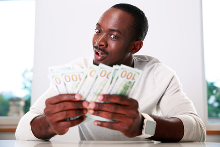 american banker: Portrait of a happy african man holding US dollars