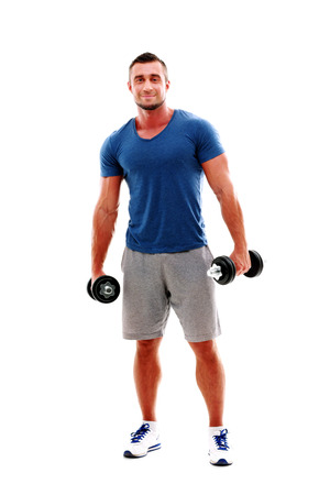 Full length portrait of a happy muscular man standing with dumbbells Stock Photo