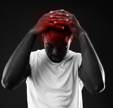 Pensive african man touching his head over black background photo