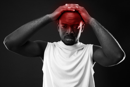 Frustrated african man touching his head over black background photo