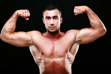 Serious muscular man showing his biceps on black background photo
